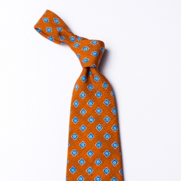 Orange tie  with a blue floral pattern